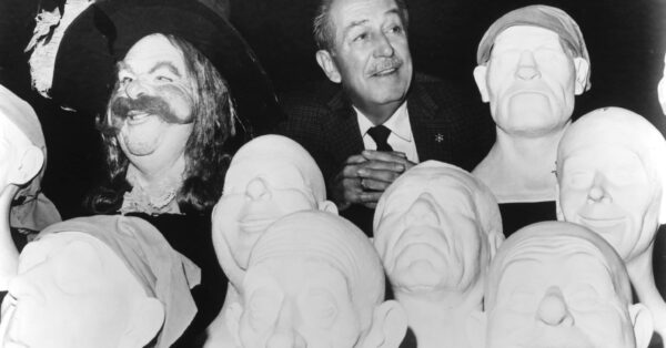 Walt Disney poses with sculpted models that were used to create Audio-Animatronics figures for the Pirates of the Caribbean attraction